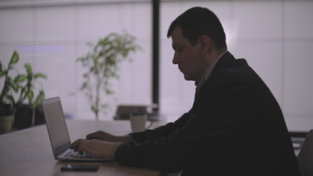 Middle-aged man in the office at the table, working on the computer video