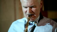 Middle-aged man saxophonist 50 years playing a musical instrument saxophone. video