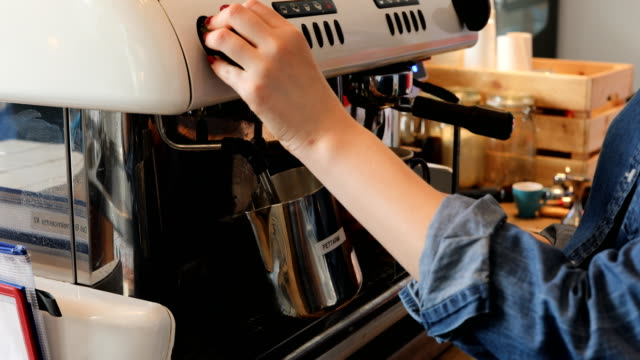 Midsection Of Female Barista Steaming Milk At Cafe video