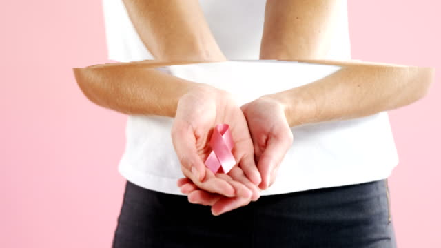 Mid-section of woman holding breast cancer awareness ribbon video
