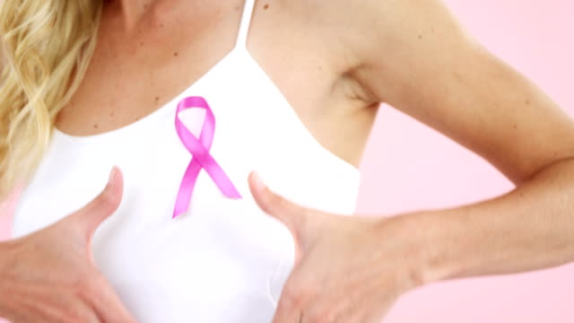 Mid-section of woman showing breast cancer awareness ribbon video