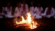 Midsummer night. Young people in Slavic clothes sitting near the bonfire. video