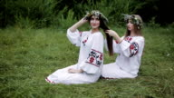 Midsummer. Two girls in the Slavic clothes weave braids in the hair near the fire. video