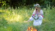 Midsummer. Woman weaving a wreath near the fire. video