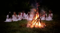 Midsummer. Young people in Slavic clothes sitting in the woods near the fire. video
