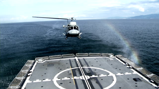 Military helicopter lands on the deck of a battleship video