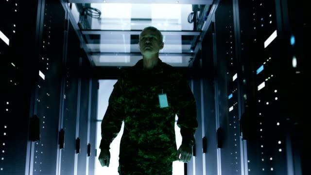 Military Man Walks Through Data Center with Working Rack Servers. video