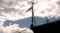 Military Ship bow flag backlit on dramatic sky video