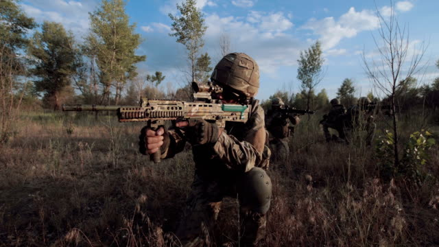 Military troop sitting and aiming video
