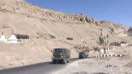Military trucks drive on the road at Lamayuru in Leh Ladakh, Jammu and Kashmir, India video