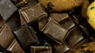 Milk and dark chocolate tiles on a wooden background.chocolate bars close up video