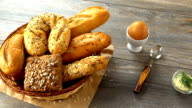 Milk, butter, cookies, egg, and fresh bread on a rustic wooden table. Countryside breakfast video