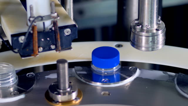 Milk drops on a surface of a bottle capping equipment. video