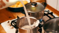 Milk is Poured into a Pan on the Stove in a Home Kitchen. Slow Motion video