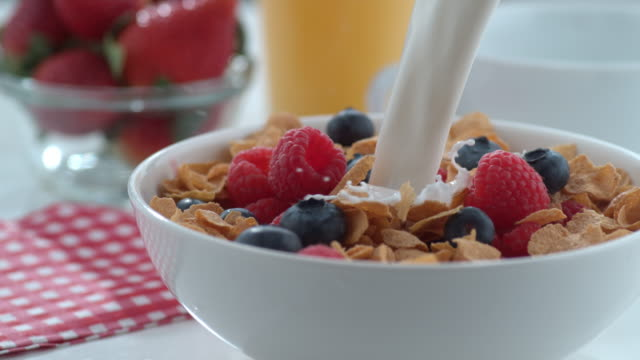 Milk pouring into bowl of cereal and berries video