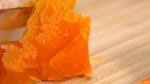 Mimolette cheese cut with cheese knife on a bamboo board video