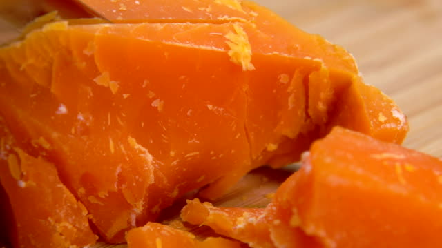 Mimolette cheese cut with cheese knife on a board video