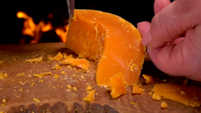 Mimolette cheeses cut with cheese knife on a board video