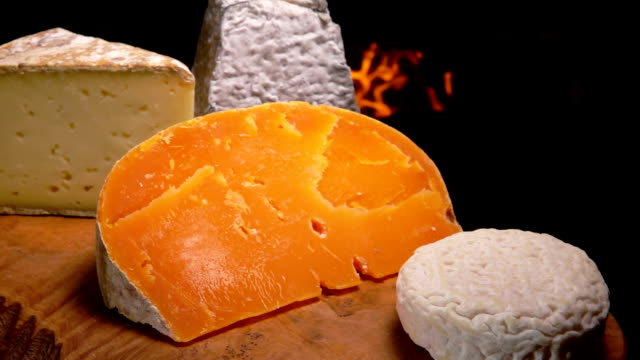 Mimolette cheeses on a board near the burning fireplace video