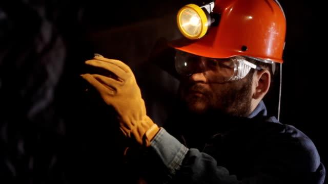 Miner examines chunk of coal video