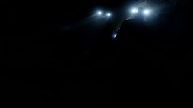 Miners Wearily Search Through a Dark Cave Illuminated By Only Their Headlamps. video
