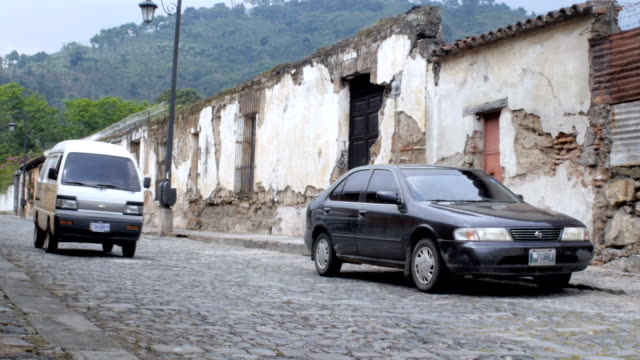 A mini bus drives down the cobble stone streets of Antigua, Guatemala video