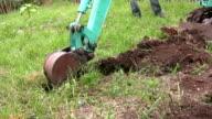 Mini digger excavating soil unearthing scrap metal video