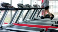 Mirror reflection of muscular sportsman exercising on treadmill at fitness video