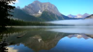Mirrored Image of mountains on lake surface with mist rising video