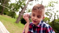 Mischievous Boy listening on tin can phone in his hands video