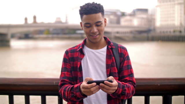 Mixed race British man texting video