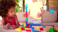 Mixed race children friends playing with building blocks video