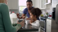 Mixed race couple and daughter eating breakfast in kitchen, shot on R3D video