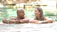 Mixed race couple at resort swimming pool video