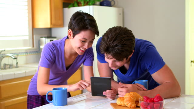 Mixed race couple enjoying reading the news together video