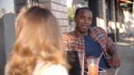 Mixed race couple talking at a table outside a coffee shop video