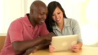 mixed race couple using tablet pc together video