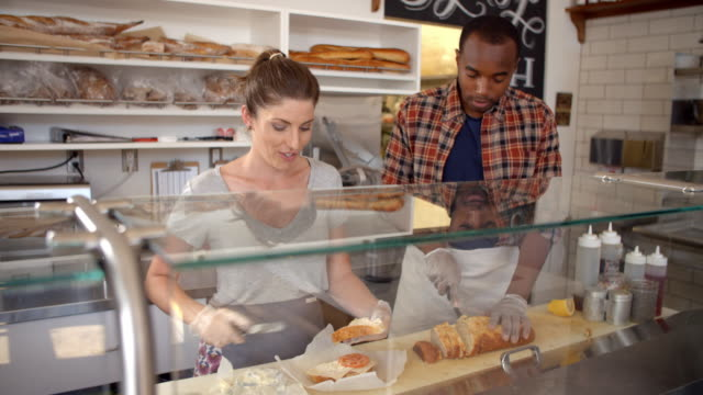 Mixed race couple working behind counter at a sandwich bar video