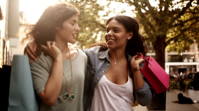 Mixed race friends walking in city with shopping bags video