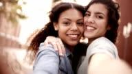 Mixed race girl friends taking selfie video