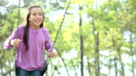 Mixed race girl on swing in park video