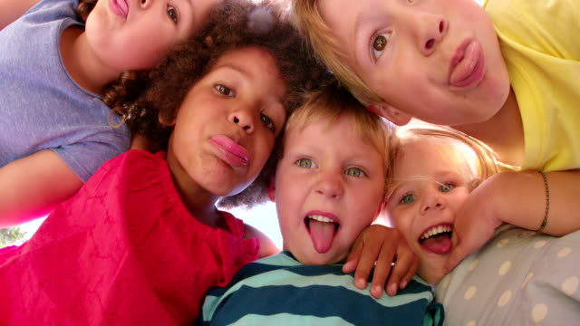 Mixed race kids posing above the camera smiling playfully video
