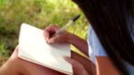 Mixed Race Person sitting at tree writing in journal video
