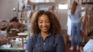 Mixed race woman in design studio walks in to focal plane video