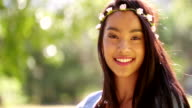 Mixed Race Woman with flowers in hair smiling in camera video