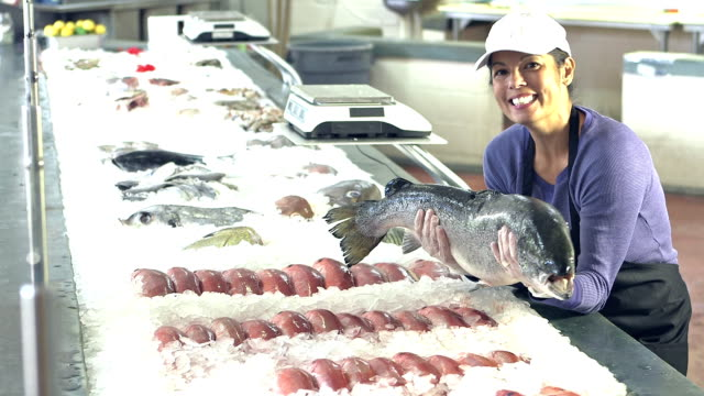 Mixed race woman working in seafood market with big fish video
