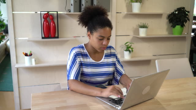 Mixed race woman works with computer at the office video