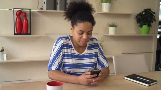 Mixed race young woman texting sms on the smartphone video