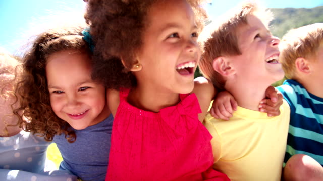 Mixed racial group of friendly children laughing together video