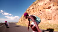Mixed racial group of teen skateboarders racing downhill together video